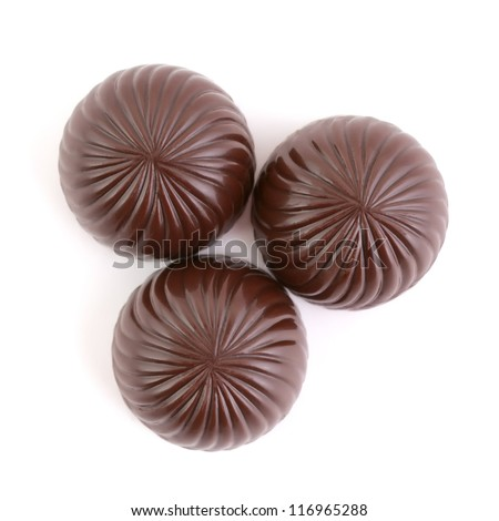 Three delicious chocolate candies isolated on white. Top view. - stock photo