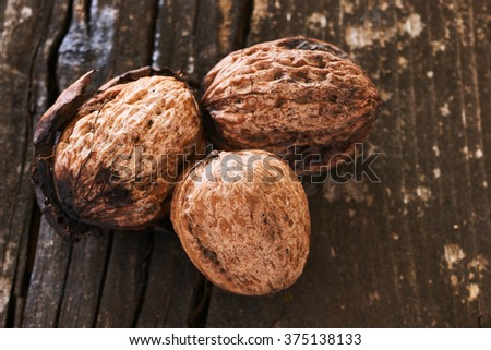 Three delicious freshly harvested nuts on an old wooden table