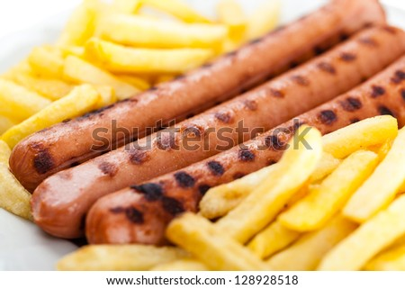 three delicious wurstel on a white plate with french fries - stock photo