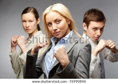 Three determined businesspeople in defense pose