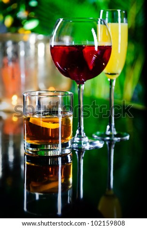 Three different beverages, glass of whiskey, glass of red wine and yellow cocktail - stock photo