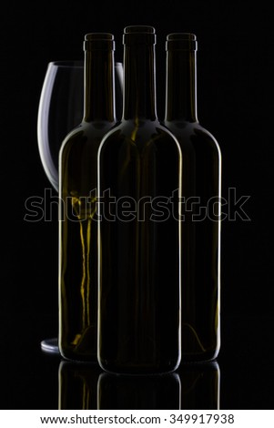 Three different bottles of wine on the black glass. - stock photo
