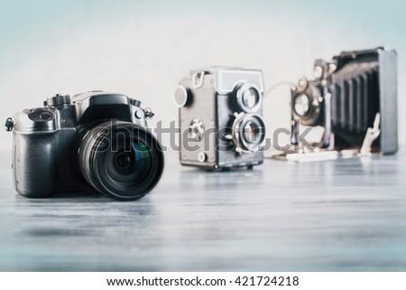 Three different cameras on grey wooden desktop - stock photo