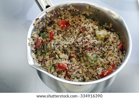 Three different color quinoa seeds after cooked in a pan with sweet red bell pepper, basil, sunflower seeds, and cucumber. Prepared quinoa dish in a stainless steel pan