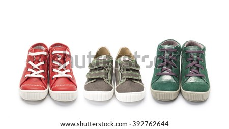 Three different colored pairs of shoes, lace and velcro straps, on a white background