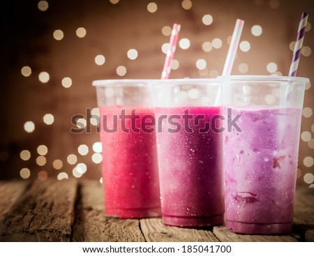 Three different colorful berry smoothies with twinkling party lights standing in a row on a rustic wooden counter top at a restaurant or bar - stock photo
