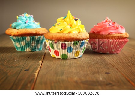 Three different colors cupcakes on a wooden table, blue, yellow and pink. - stock photo