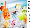 Three different colourful tropical fruit bubble tea sorts served chilled on a bed of crushed ice as a welcome refreshment at a beachfront resort - stock photo