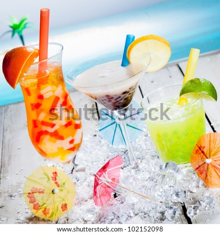 Three different colourful tropical fruit bubble tea sorts served chilled on a bed of crushed ice as a welcome refreshment at a beachfront resort