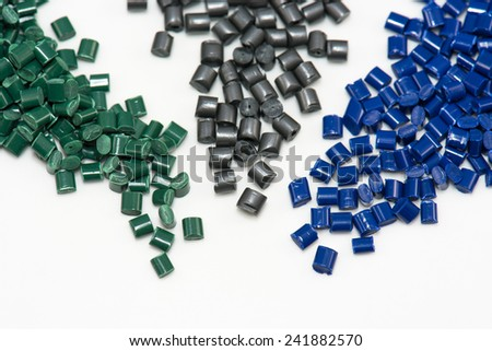 three different dyed plastic polymer pellets on white - stock photo