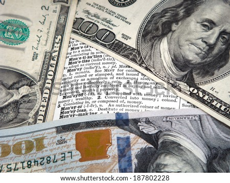 Three Different Hundred Dollar Notes Positioned Around Definitions Of Money. Cropping of image is close to bring importance to the definitions of this vintage dictionary. - stock photo