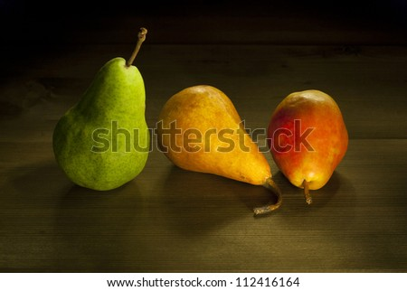 three different ripe pears, rustic wooden table - stock photo