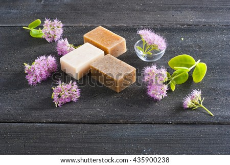 three different salt soaps and pink flowers on black wood background