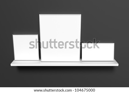Three different sized aluminum frames with blank images, standing besides each other on a white shelf on a dark background.