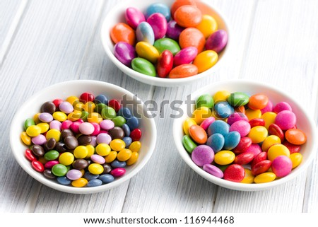 Three different sizes of colorful candies in ceramic bowls - stock photo