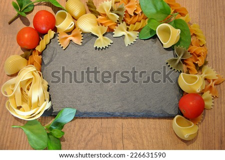 Three different types of colored pasta on wood - stock photo
