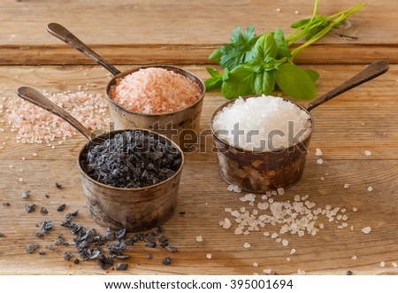 Three different types of salt in silver containers on a worn out wooden surface. White sea salt, pink Himalayan and black Maldon. - stock photo