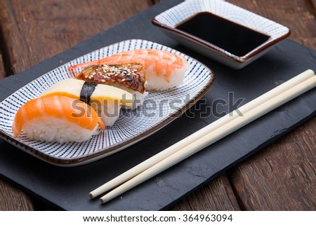 Three different types of sushi. Nigiri. Served on a black plate - stock photo
