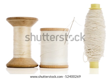 three different white spools of thread on white - stock photo