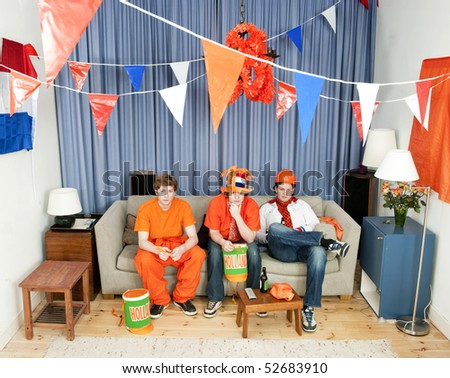 Three disillusioned sports fans on a couch watching a game of their national team - stock photo