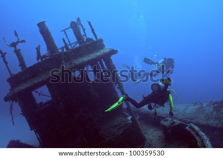 """Three divers are exploring the wreck of a tugboat.  Shot in """"Wreck Alley"""" in the  B.V.I.'s. - stock photo"""