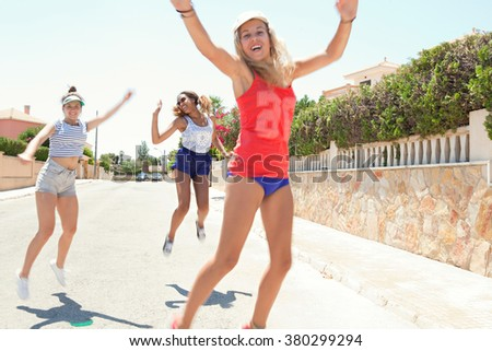 Three diverse joyful teenagers girls friends having fun together in a suburban home exterior street jumping up in the air, sunny outdoors. Sporty action living. Adolescents enjoying holiday, smiling. - stock photo
