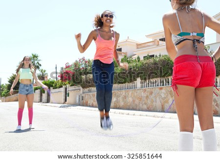Three diverse teenager girls friends playing and having fun in a suburban street on a sunny day, outdoors. Adolescents recreation lifestyle, holiday weekend break. Street exterior with young people. - stock photo