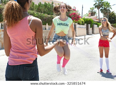 Three diverse teenager girls friends playing and having fun in a suburban street with buildings, outdoors. Adolescents recreation lifestyle, holiday weekend break. Street exterior with young people. - stock photo