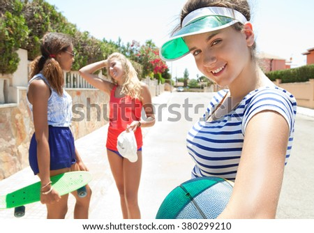 Three diverse teenagers girls friends having fun together in suburban home exterior street with skateboard and basketball, sunny outdoors. Sporty active living. Adolescents enjoying holiday, smiling. - stock photo