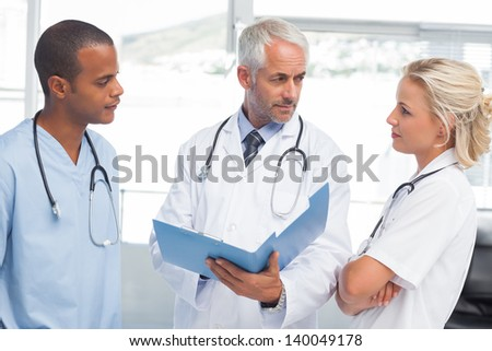 Three doctors examining a file in a bright office - stock photo