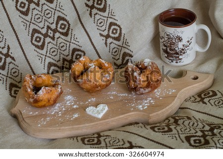Three donuts with cherry on the cutting board with sugar heart. One cup with a flower. Romantic breakfast for love wife.  - stock photo