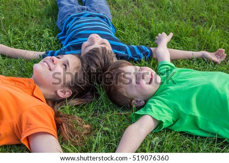 Three dreaming kids lying down together on green grass meadow