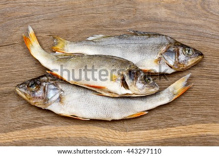 Three dried fishes on a vintage wooden bacground.