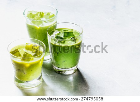 Three Drinking Glasses Filled with Healthy Green Smoothie Shake Made from Avocado and Kiwi, Cooled with Ice on Shiny Silver Metal Surface with Copy Space - stock photo