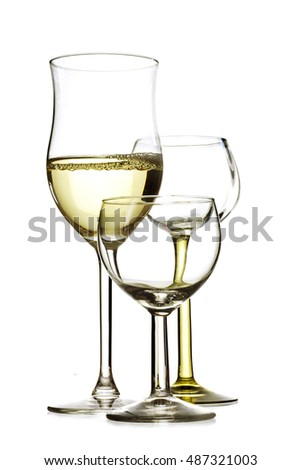 three drinking glasses, one is filled with white wine, the others are empty, isolated on a white background