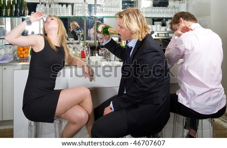 three drunken persons sitting on a bar stool and drinking champagne - stock photo