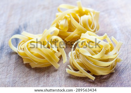 Three dry tagliatelle nests on a wooden background - stock photo