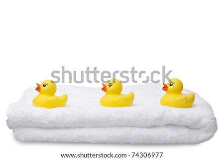 Three Ducks in a Row.  Three yellow rubber ducks in a row on a fluffy white towel isolated against a white background with copy-space.