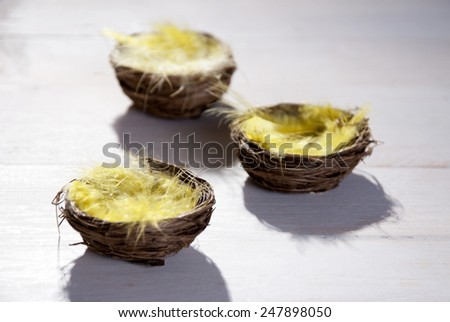 Three Easter Baskets Or Nests With Yellow Feathers in Sunny Light With Copy Space Free Text Or Your Text Here For Happy Easter Greetings Or Easter Decoration Close Up Or Macro Wooden Background - stock photo