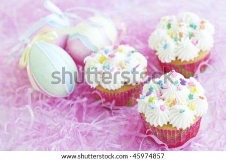 Three Easter cupcakes with colorful pastel candy sprinkles with pastel Easter eggs, horizontal with pink Easter grass background, selective focus - stock photo