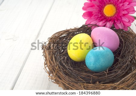 Three Easter Eggs in a Twig Bird Nest with Bright Pink Faux Gerbera Daisy on white board background with room or space for copy, text.  Horizontal closeup. - stock photo