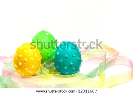 Three Easter eggs with speckles and glitter in a multicolored ribbon nest. - stock photo