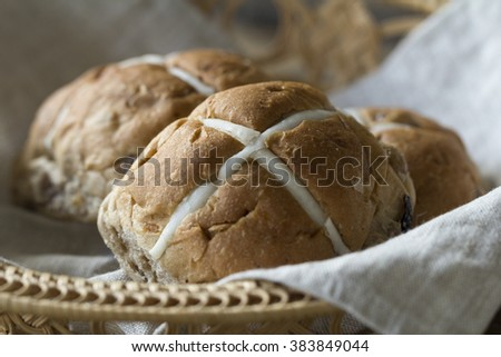 Three Easter hot cross buns in a basket on a rustic wooden table - stock photo