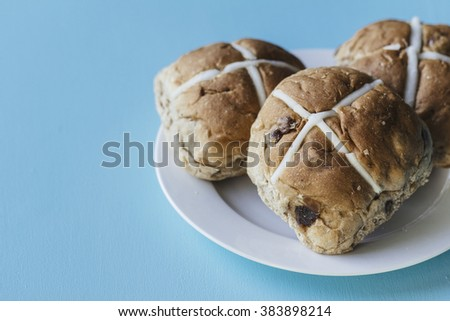 Three Easter hot cross buns on a white plate on a blue background - stock photo
