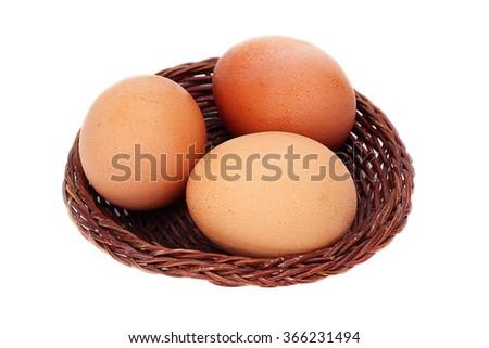 three eggs in basket isolate - stock photo