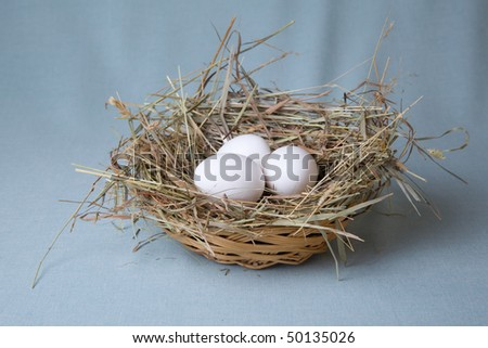 three eggs lies in basket at hay