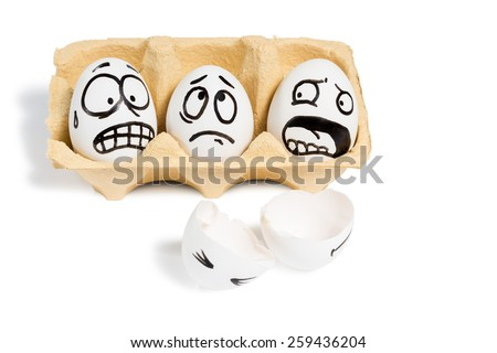 Three eggs with frightened faces looking at a broken egg lying near isolated on white background - stock photo