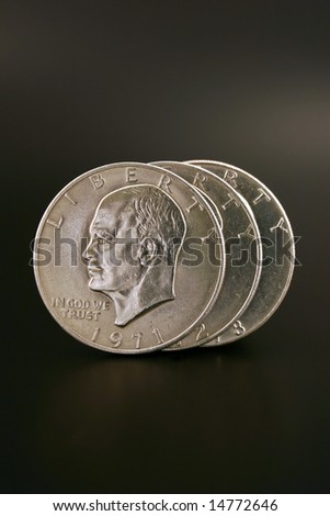 Three Eisenhower silver dollars isolated on a black background - stock photo