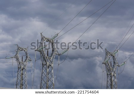 three electrical pylons on the background of a stormy sky