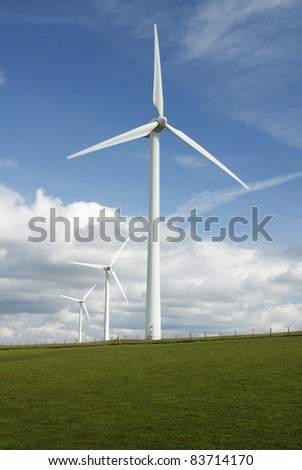 Three electricity generating wind turbines on a green hillside with a blue sky and fluffy white clouds - stock photo